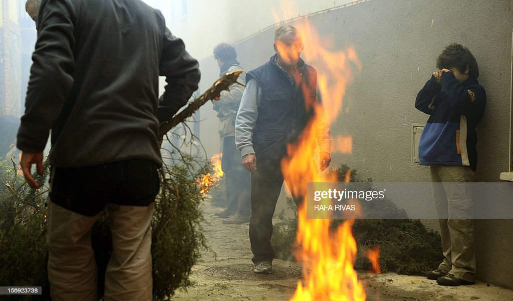 A boy protects his eyes from the the smoke as bonfires with rosemary burn during the celebration of the 'Procession of smoke' with San Andres, Saint Patron of Arnedillo on November 25, 2012, in the northern Spanish village of Arnedillo.