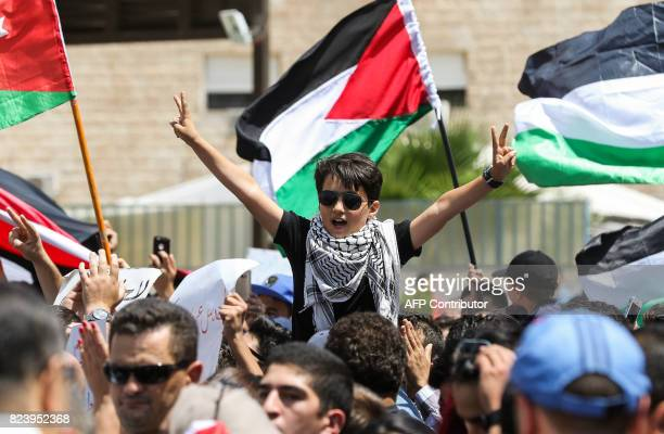 A boy protester wearing sunglasses and a keffiyeh flashes the victory gesture past Jordanian and Palestinian national flags during a demonstration...