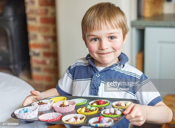 Boy proudly holding tray of Easter cakes