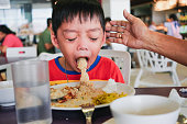 Boy puking on plate after eating lunch meal with helping hand