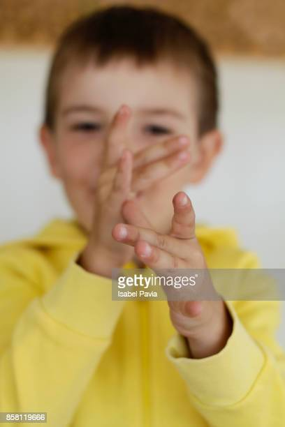 Boy (5-) pulling face, holding hands to nose