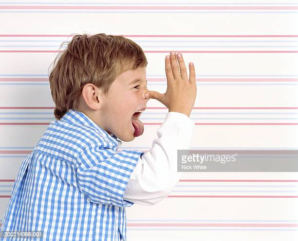 Boy (5-7) pulling face, holding thumb to nose, side view