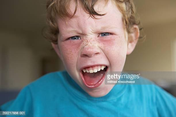 Boy (4-6) pulling face, portrait, close-up