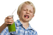 A young boy looking very disgusted holding a green smoothie. Isolated on white.