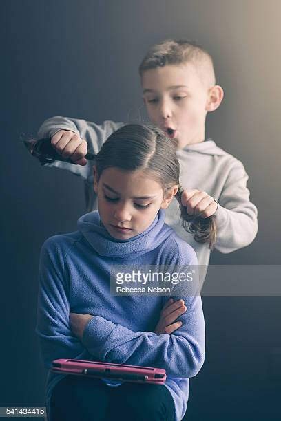 boy pulling girl's pigtails