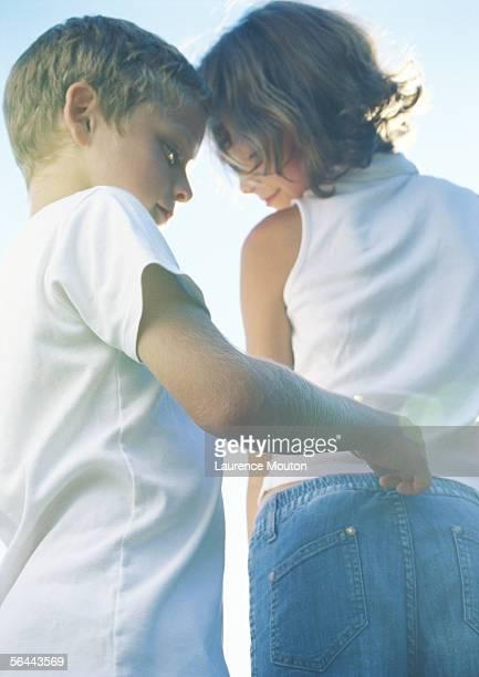 Boy pulling on girl's belt loop