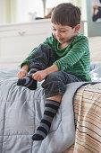Boy pulling on socks in bedroom