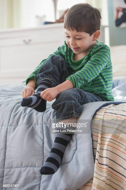 Boy pulling on socks in bedroom