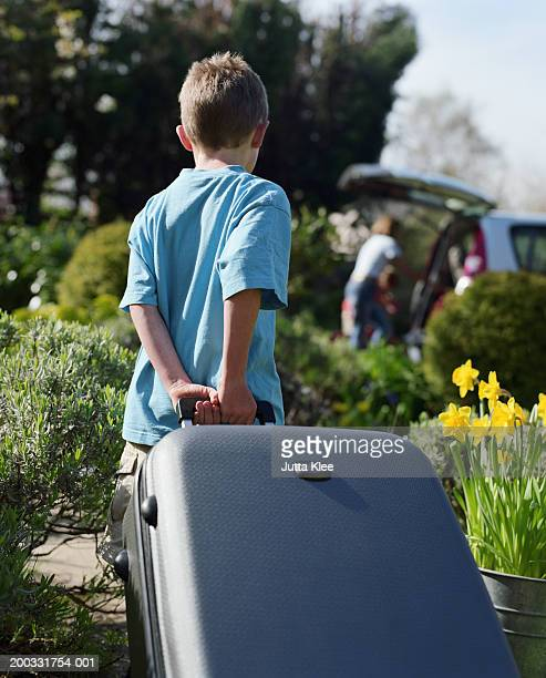 Boy (5-7) pulling suitcase in garden, mother loading car in background
