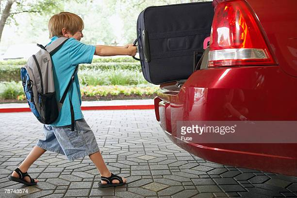 Boy Pulling Suitcase out of Car Trunk