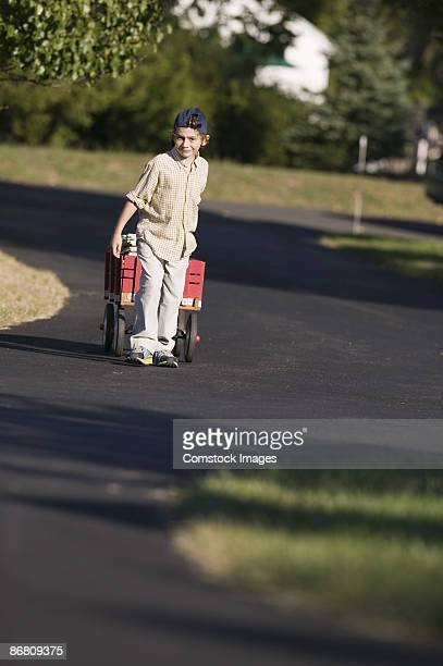 Boy pulling wagon filled with newspapers