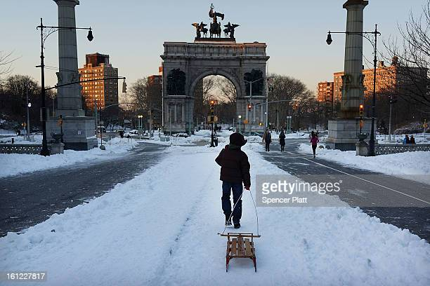 A boy pulls a sled through a snowy Prospect Park in Brooklyn the morning after a massive snow storm on February 9 2013 in New York City New Yorkers...
