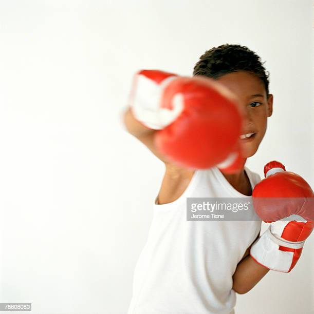 Boy punching with boxing gloves