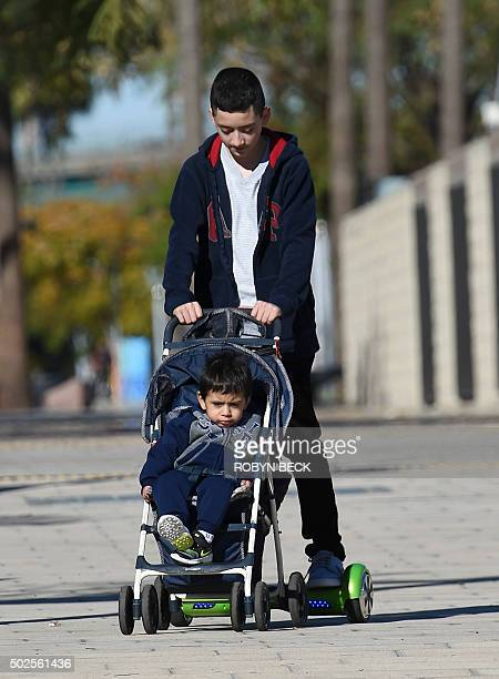 A boy pushes a child in a stroller while riding a hoverboard the day after Christmas in San Pedro California December 26 2015 Reports of some...