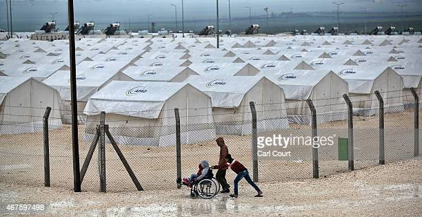 A boy pushes a wheelchair in Suruc refugee camp on March 25 2015 in Suruc Turkey The camp is the largest of its kind in Turkey with a population of...