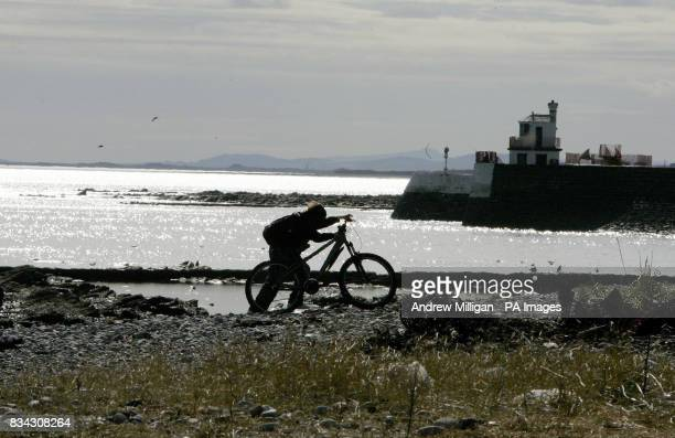 A boy pushes his bike along the reopened Arbroath beach Angus after body parts were found yesterday