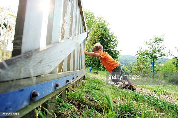 A boy pushes the gate
