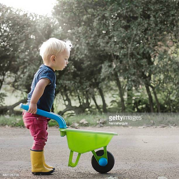 Boy pushing a toy wheelbarrow