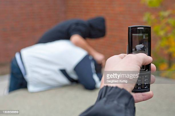 Boy pushing another boy down onto a table tennis table being filmed with a mobile phone