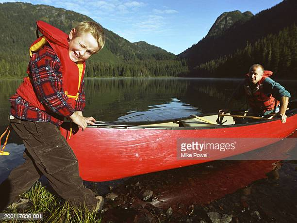 Boy (7-9) pushing canoe in to lake with father, portrait