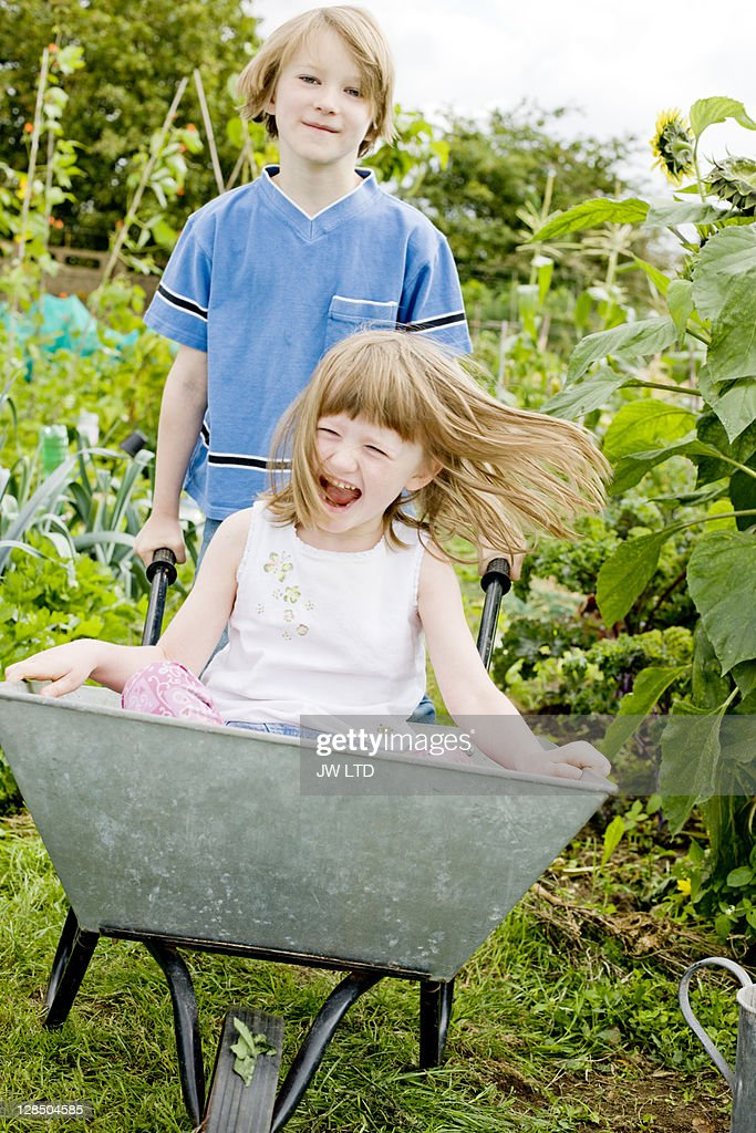 Boy pushing girl in wheelbarrow : Stock Photo