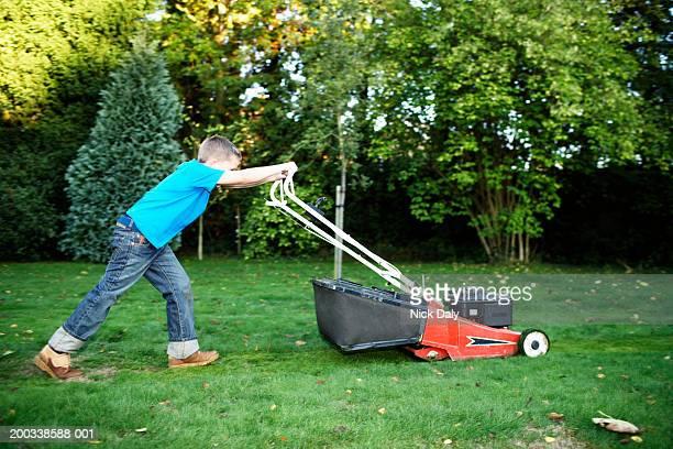 Boy (7-9) pushing lawnmower, side view