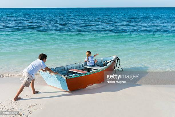 boy pushing small boat with little girl into ocean