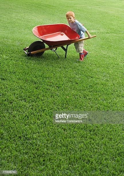 Boy pushing wheelbarrow across grass