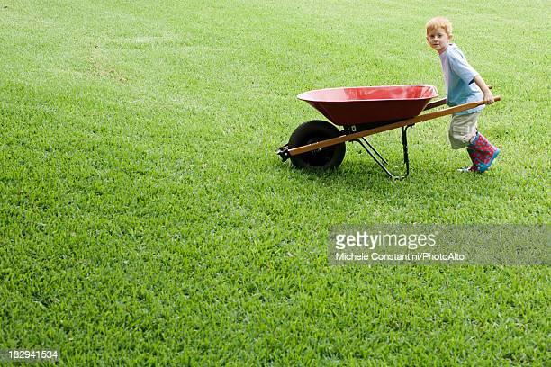 Boy pushing wheelbarrow