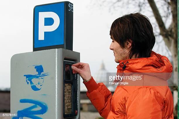A boy puts coins in a parking meter placed in front of the St Peter's cupole March 10 in Rome