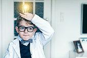 Boy puts light bulb on top head and gets idea