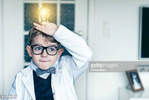 Boy puts light bulb on top head and gets idea