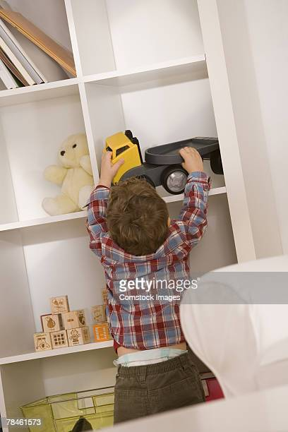 Boy putting away toys