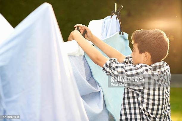 Boy putting bed sheets onto homemade tent in garden