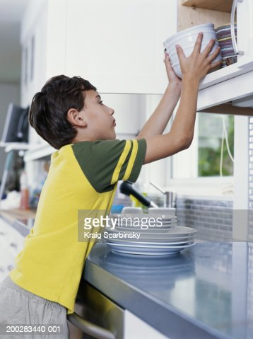 Boy (6-8) putting bowls away in kitchen cupboard, side view : Foto de stock