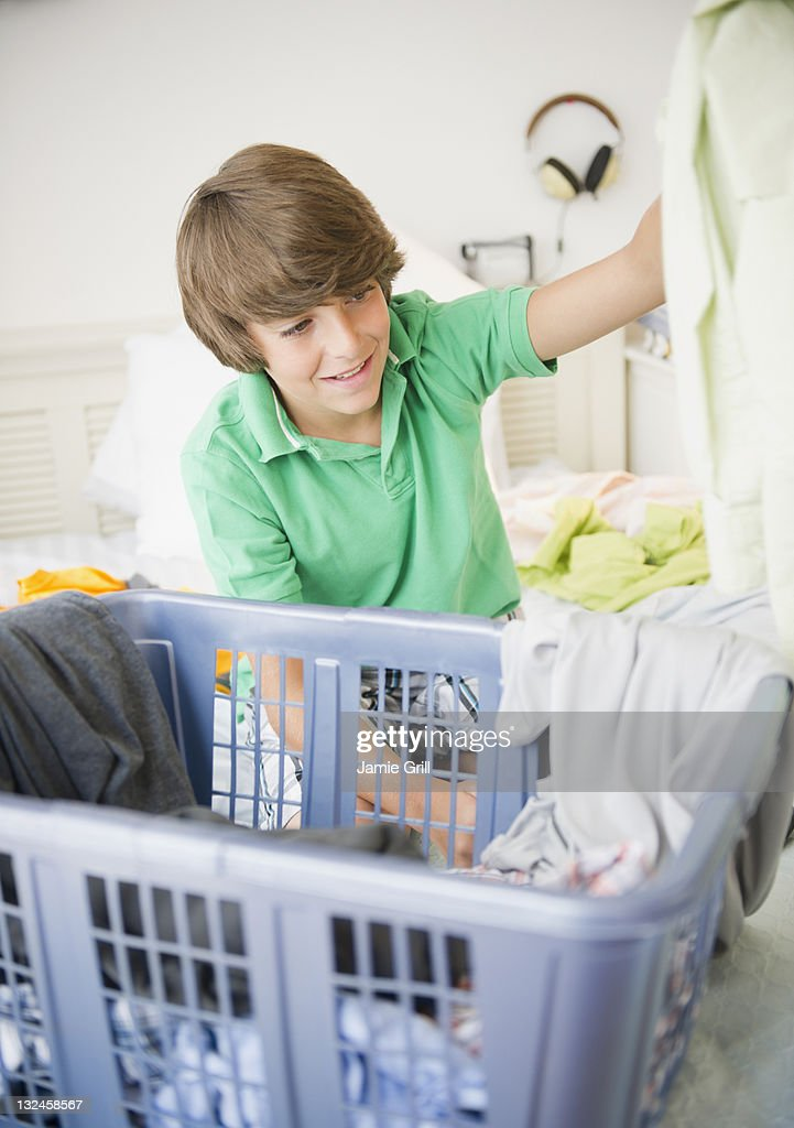 Boy putting clothes into laundry basket : Stock Photo