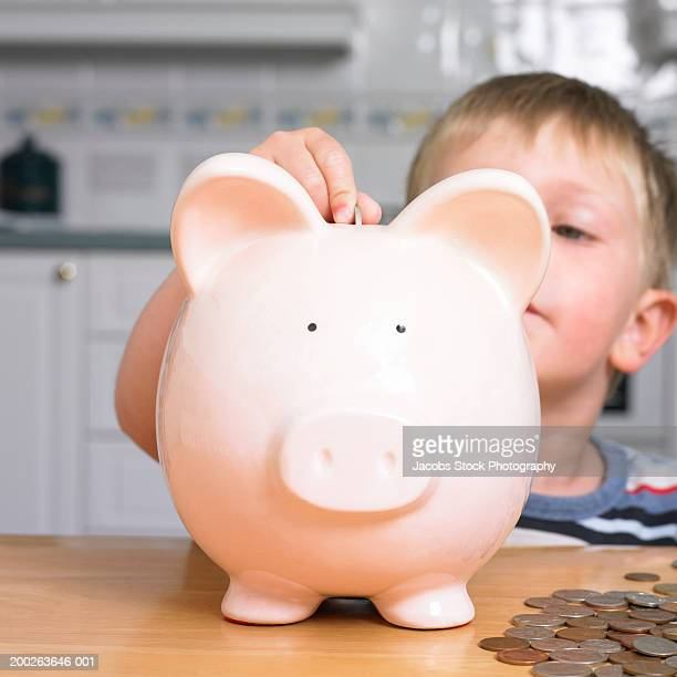 Boy (2-4) putting coin in piggy bank, close-up