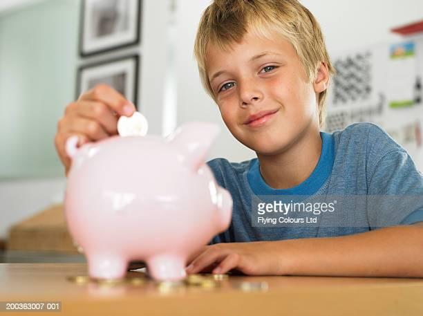 JUNGEN (7 und 9) setzen Münze in Sparschwein, Lächeln, Porträt