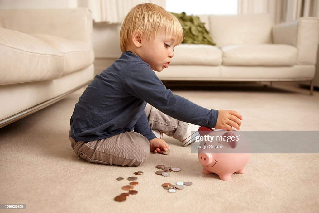 Boy putting coins in piggy bank : Stock Photo