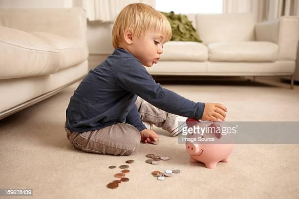 Boy putting coins in piggy bank