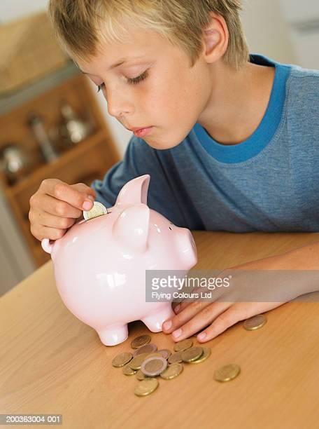 Boy (7-9) putting euro coin into piggy bank
