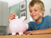Boy (7-9) putting euro coin into piggy bank, smiling