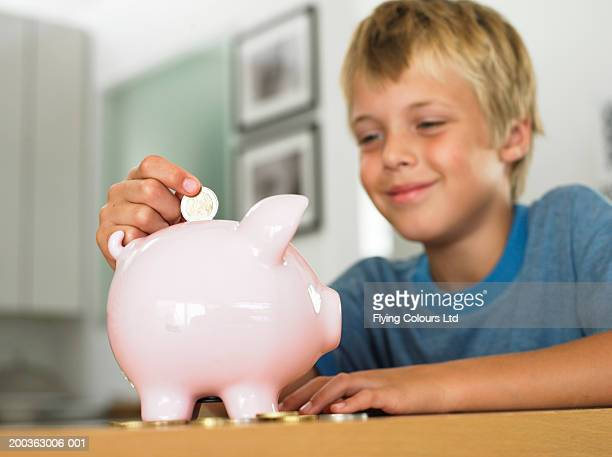 Boy (7-9) putting euro coin into piggy bank, smiling