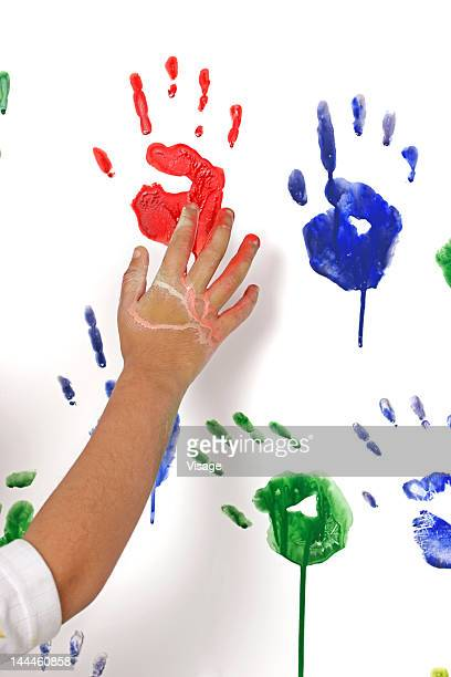 Boy putting hand prints on the wall using colours