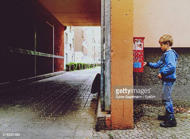 Boy Putting Letter In A Mailbox