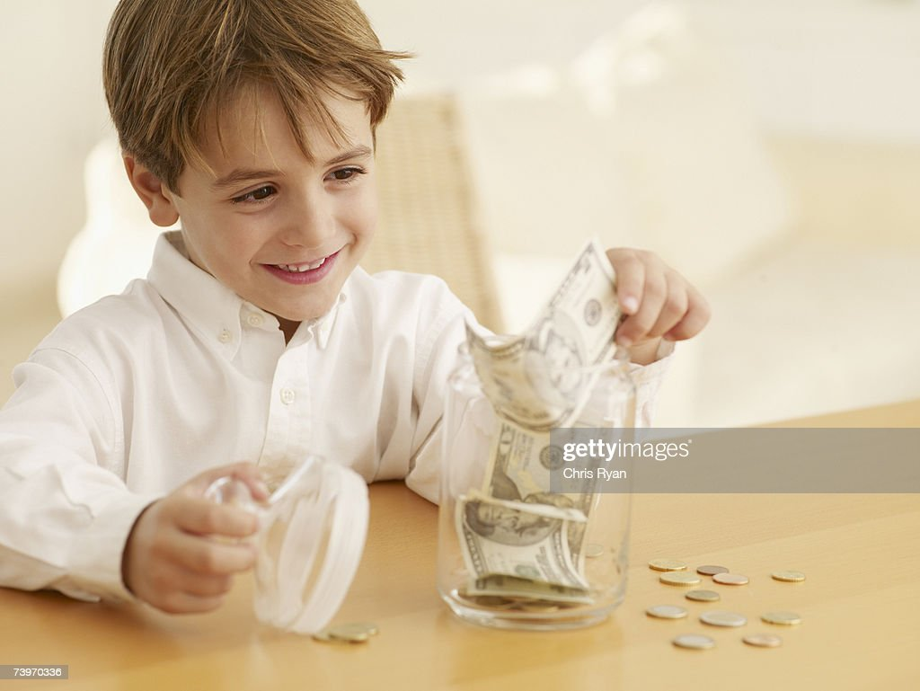 Boy putting money into a cookie jar : Stock Photo