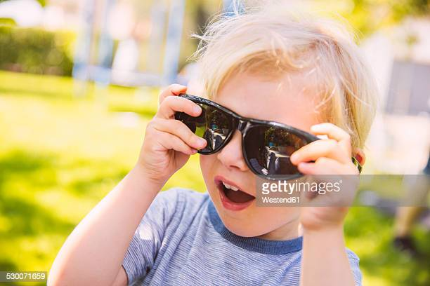 Boy putting on giant black sunglasses in garden
