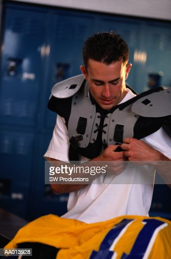 Boy Putting on His Shoulder Pads in a Locker Room