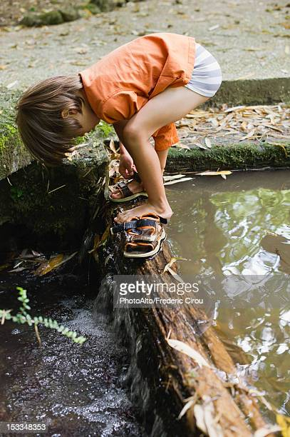 Boy putting on sandals by flowing water