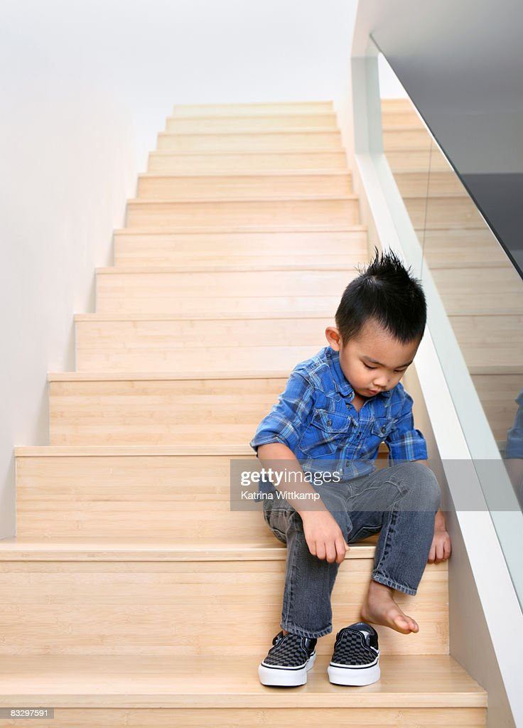 Boy putting on shoes on steps of his home. : Stock Photo